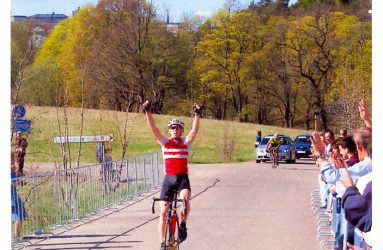 En cyklist sträcker armarna i luften när han går i mål